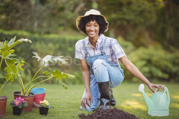 Glimlachende vrouw hurken tuin naar camera vrouw Stockfoto © wavebreak_media