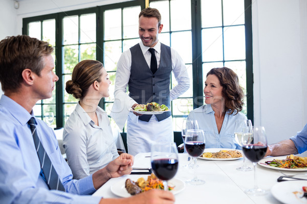 Waiter serving salad to business people Stock photo © wavebreak_media
