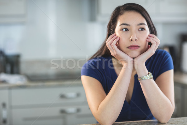 Young woman daydreaming in kitchen Stock photo © wavebreak_media