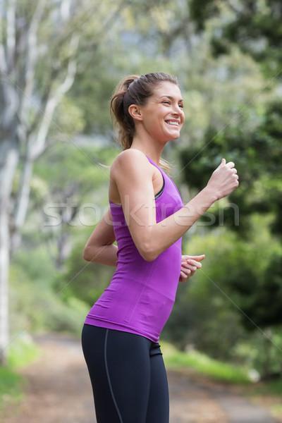 Happy young woman running on footpath Stock photo © wavebreak_media