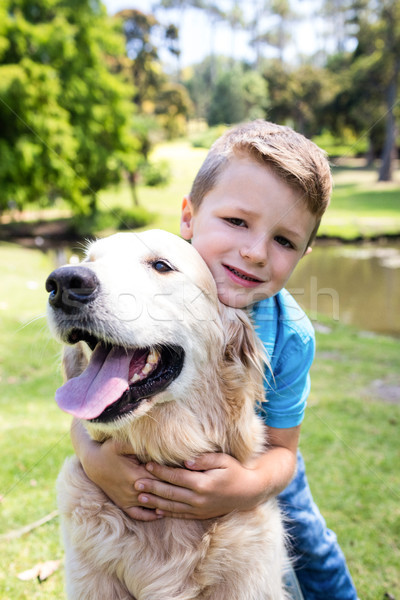 Smiling boy with his pet dog in the park Stock photo © wavebreak_media