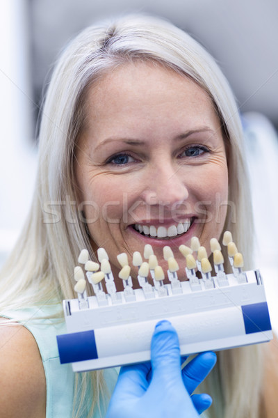 Dentist holding teeth shades while female patient smiling Stock photo © wavebreak_media