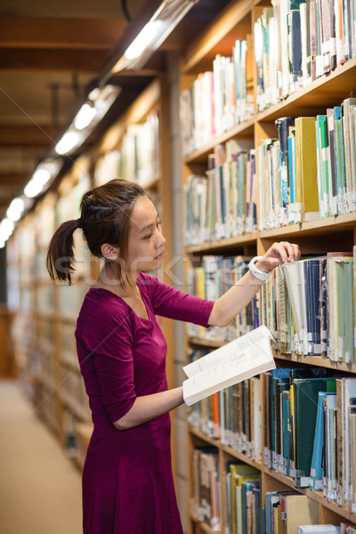 Young woman selecting book in library Stock photo © wavebreak_media