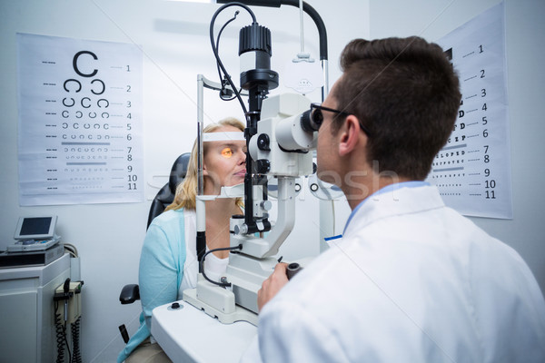 Optometrist examining female patient on slit lamp Stock photo © wavebreak_media