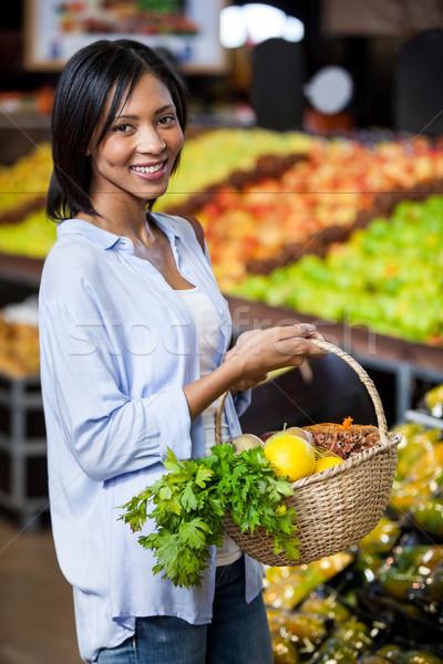 Smiling woman holding fruits and vegetables in basket Stock photo © wavebreak_media