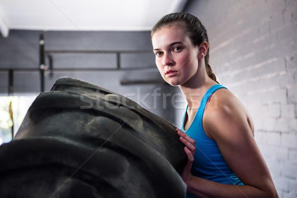 Portret kobiet sportowiec popychanie opon siłowni Zdjęcia stock © wavebreak_media