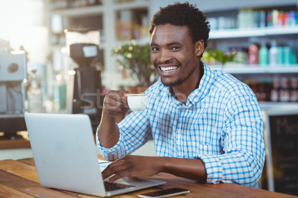 Man using a laptop while having cup of coffee Stock photo © wavebreak_media