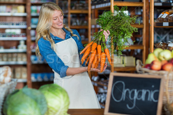 Smiling female staff holding bunch of carrots in organic section Stock photo © wavebreak_media