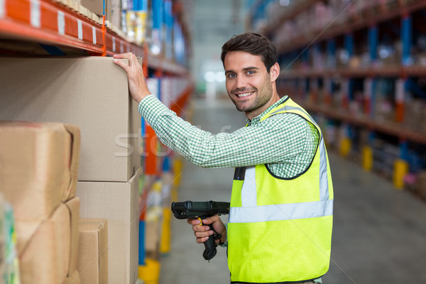 Portrait of smiling warehouse worker scanning box Stock photo © wavebreak_media