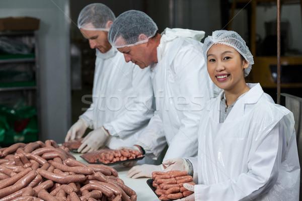 Butchers packing raw sausages Stock photo © wavebreak_media