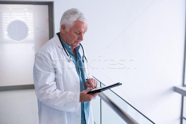 Doctor using a digital tablet in the passageway  Stock photo © wavebreak_media