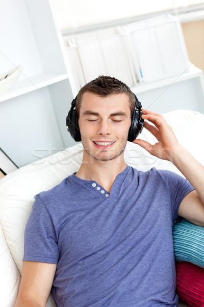 Nyugodt fiatalember zenét hallgat ül kanapé nappali Stock fotó © wavebreak_media