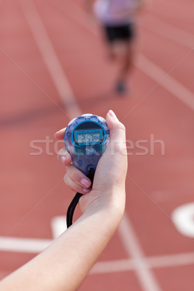 Close-up of a woman holding a chronometer to measure performances of a sprinter in a stadium Stock photo © wavebreak_media