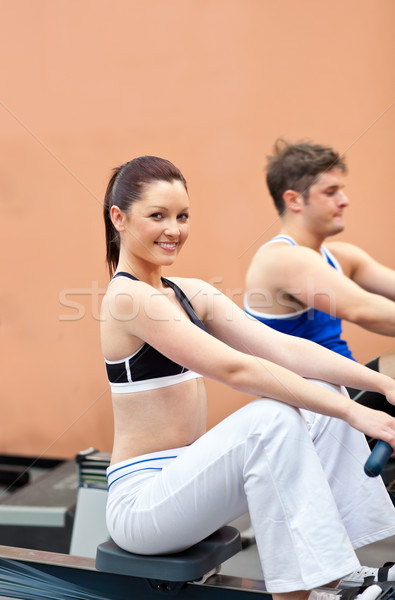 Athletic young people using a rower in a fitness center with woman smiling at the camera Stock photo © wavebreak_media