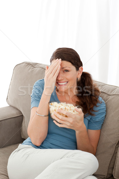 Pretty woman hiding her face while watching a horror movie at home Stock photo © wavebreak_media