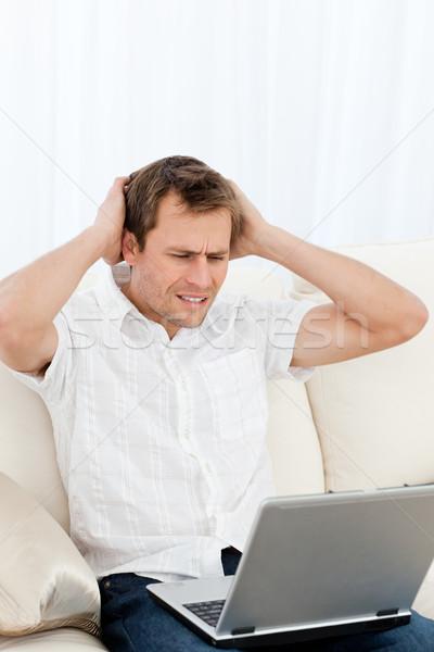 Tenso homem trabalhando laptop sessão sofá Foto stock © wavebreak_media