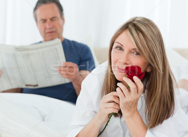 Happy woman smelling her rose while her husband is reading a newspaper at home Stock photo © wavebreak_media