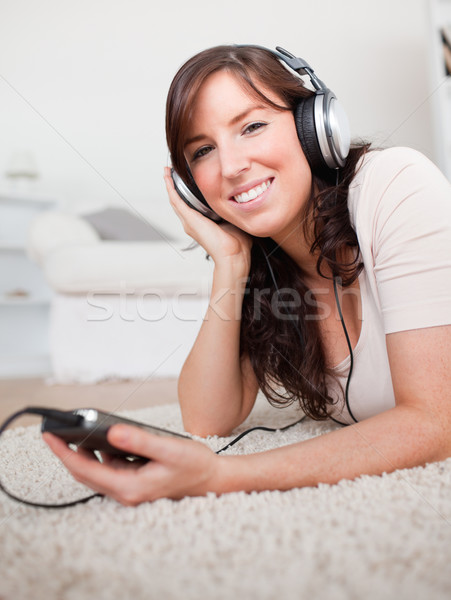 Gorgeous brunette woman listening to music with her mp3 player while lying on a carpet in the living Stock photo © wavebreak_media