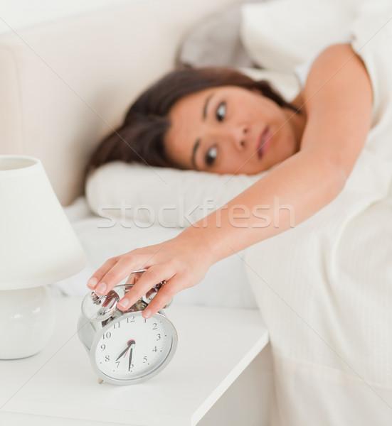 charming woman waking under sheet turning off alarm clock in bedroom Stock photo © wavebreak_media
