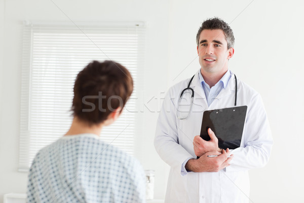 Doctor talking to a woman in hospital gown in a room Stock photo © wavebreak_media