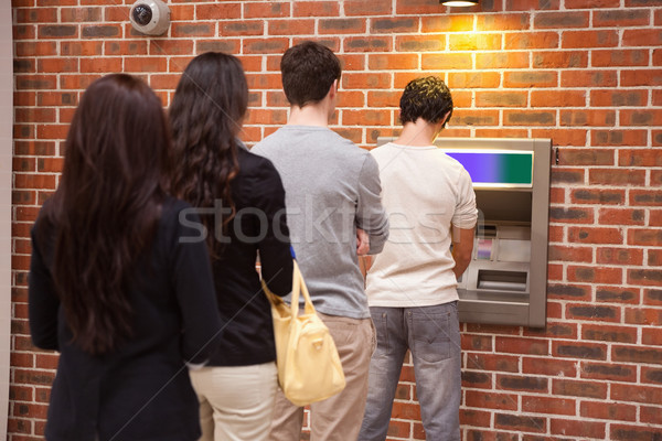 Young people queuing to withdraw cash in an ATM Stock photo © wavebreak_media