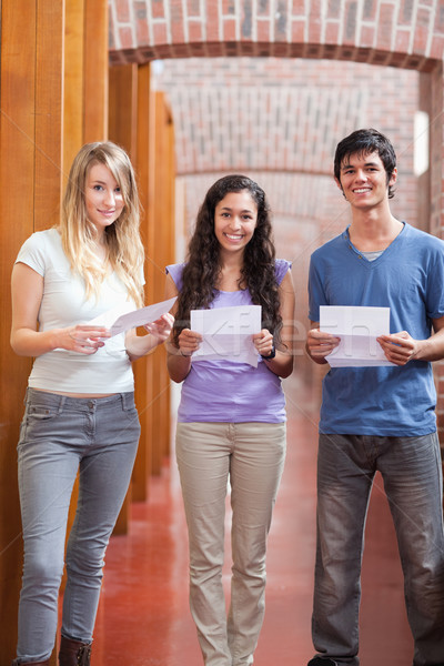 Portrait of smiling students holding a piece of paper in a corridor Stock photo © wavebreak_media