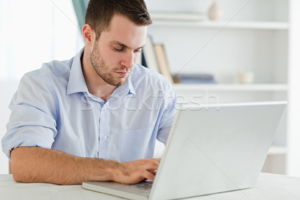 Young businessman with rolled up sleeves in his homeoffice on his laptop Stock photo © wavebreak_media