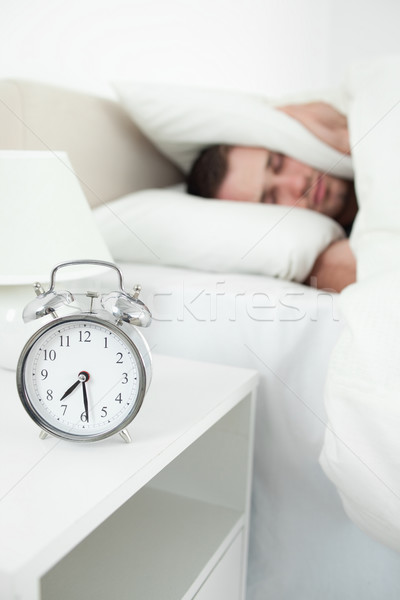 Portrait of a unhappy young man covering his ears with a pillow while his alarm clock is ringing Stock photo © wavebreak_media