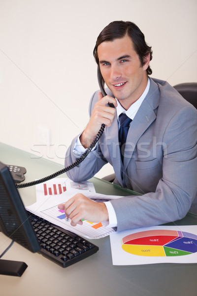Stock photo: Smiling young businessman on the phone working on statistics