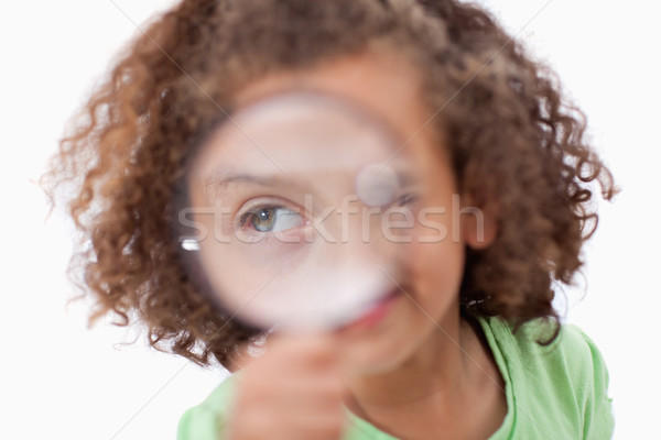 Smiling girl looking through a magnifying glass against a white background Stock photo © wavebreak_media