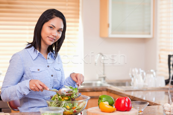 Young woman stirring her salad in the kitchen Stock photo © wavebreak_media