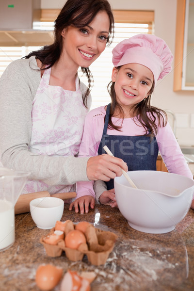 Portrait of a happy mother baking with her daughter in a kitchen Stock photo © wavebreak_media