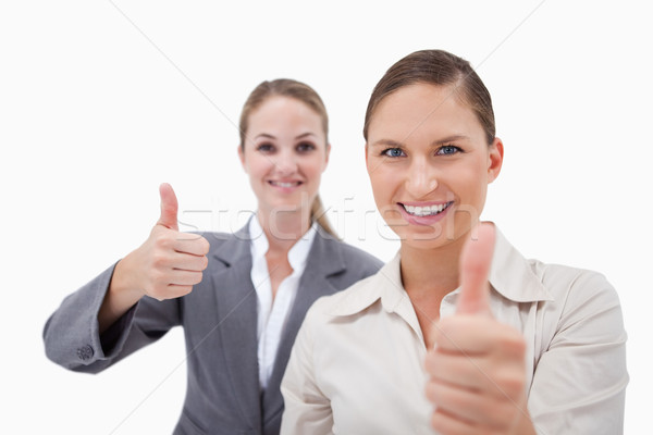 Smiling sales persons posing with the thumb up against a white background Stock photo © wavebreak_media