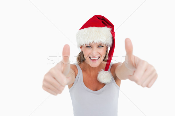Woman with the thumbs up and a Christmas hat against a white background Stock photo © wavebreak_media