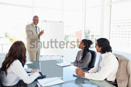 Stock photo: Young businesswoman giving a presentation while her colleagues are listening to her
