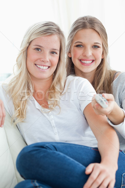 A close up shot of laughing sisters on the couch looking at the camera  Stock photo © wavebreak_media