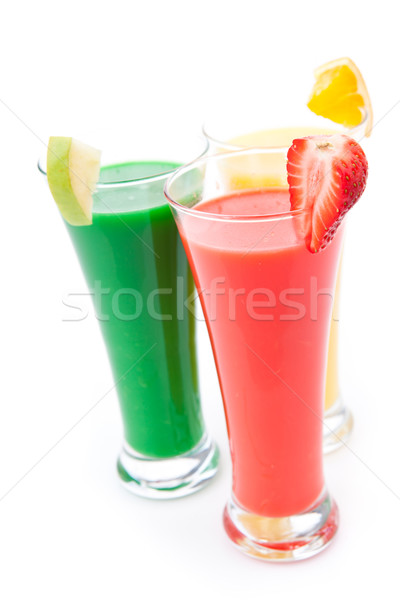 Three full glasses with fruit pieces against white background Stock photo © wavebreak_media