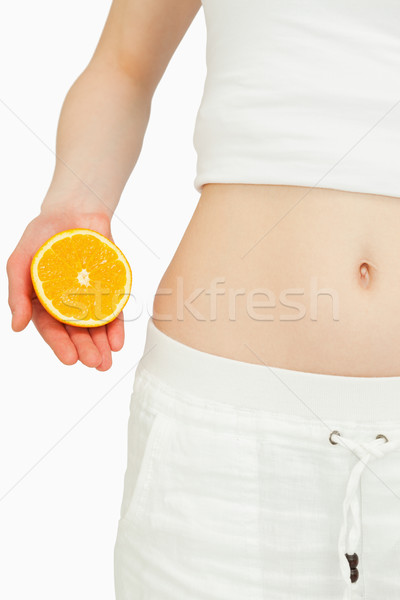 Close up of a woman placing an orange near her belly Stock photo © wavebreak_media