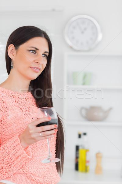 Beautiful brunette holding a glass of wine in a kitchen Stock photo © wavebreak_media