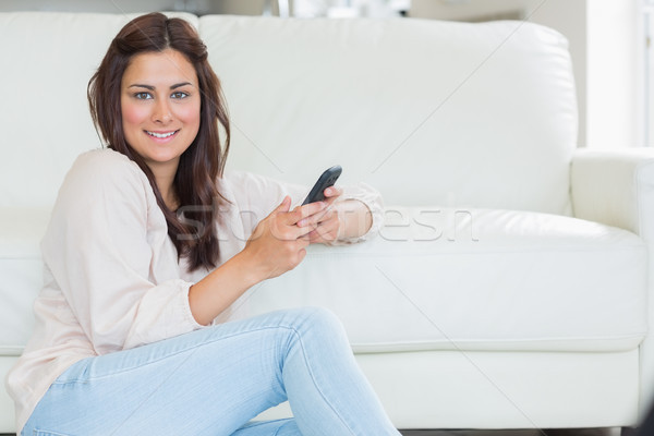 Brunette woman using her mobile phone in the living room Stock photo © wavebreak_media