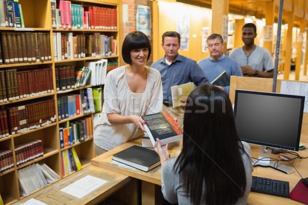 Librarian handing book to woman at library desk Stock photo © wavebreak_media