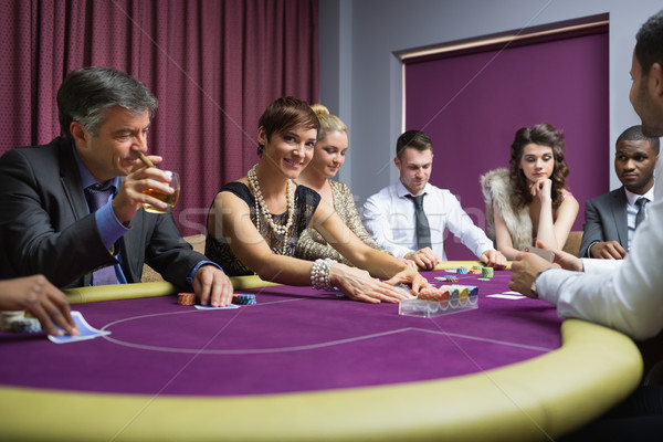 Stock photo: Woman looking up from poker game in casino