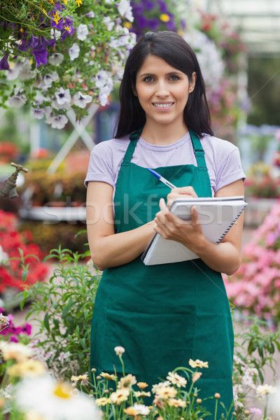 Gardener taking notes while smiling in the garden center Stock photo © wavebreak_media