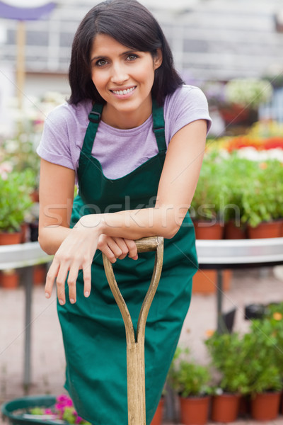 Woman working in garden center leaning on shovel outside Stock photo © wavebreak_media