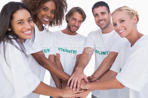 Sorridente voluntário grupo mãos juntos branco Foto stock © wavebreak_media