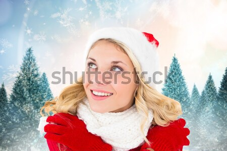Composite image of pretty girl in santa outfit holding gift Stock photo © wavebreak_media