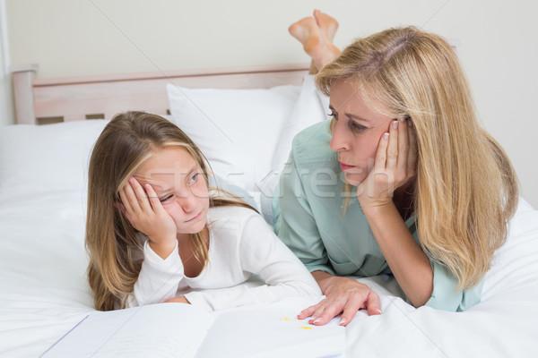 Aburrido madre hija lectura libro cama Foto stock © wavebreak_media