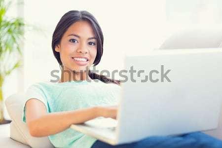 Happy girl lying on sofa using her laptop smiling at camera Stock photo © wavebreak_media
