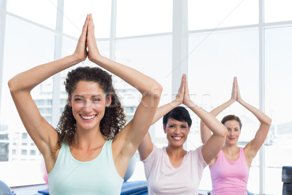 Sporty women with joined hands over head at fitness studio Stock photo © wavebreak_media