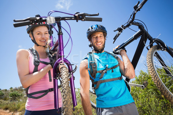 Fit couple walking down trail smiling at camera holding mountain Stock photo © wavebreak_media